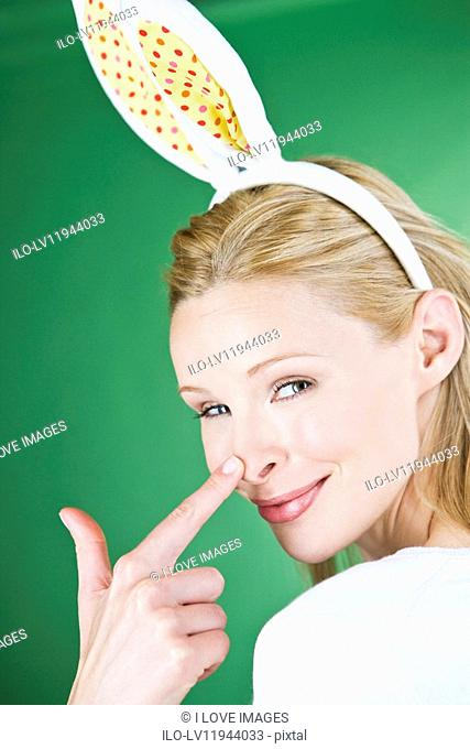A young blonde woman wearing rabbit ears, touching her nose