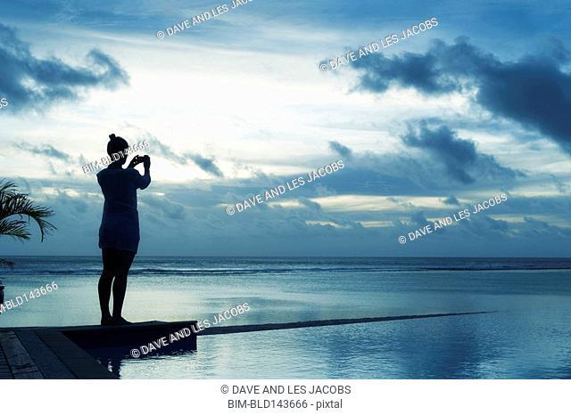 Caucasian woman taking photograph of sunset near swimming pool