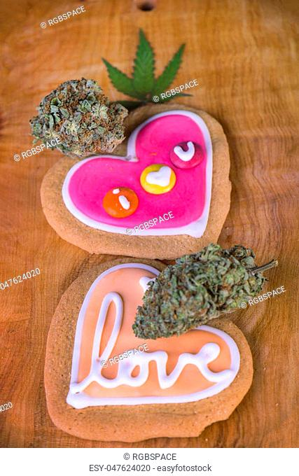 Dried cannabis nugs with with pot leaf over and baked cookies on a wood tray - infused marijuana edibles concept