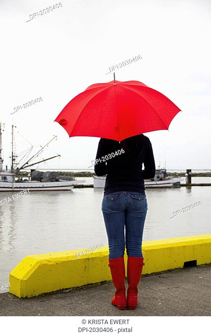 woman on a pier with a red umbrella and rain boots, richmond british columbia canada