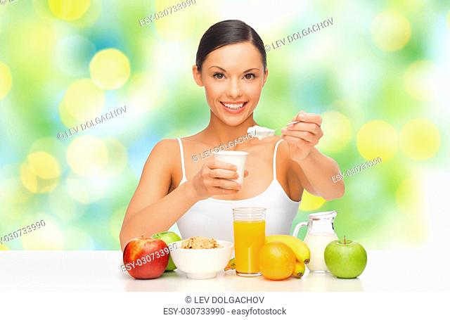 diet, healthy food and people concept - happy woman with fruits and cereals eating yogurt for breakfast over green summer lights background
