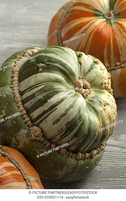 Fresh heirloom orange and green Turban squashes