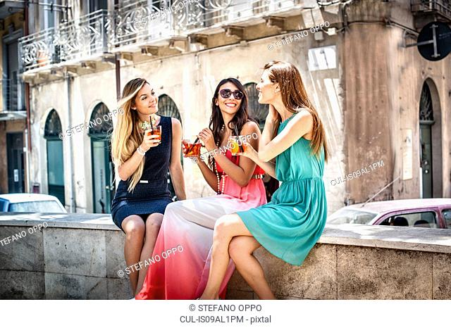 Three young fashionable female friends having cocktails on sidewalk cafe wall, Cagliari, Sardinia, Italy