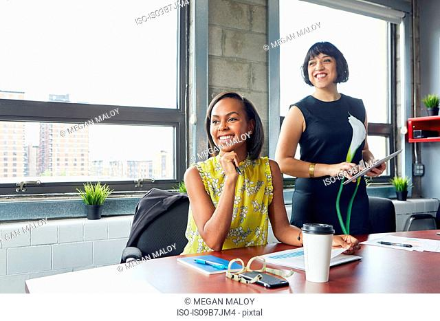 Two women in office, looking away, smiling