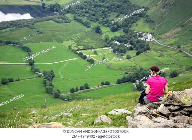 A hiker stops for lunch high up above Hartsop and Brothers Water in the Lake District