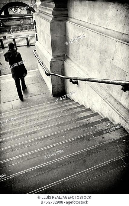 Unrecognizable man with a black coat going down stairs, big eye staring in background. Waterloo Station, Waterloo, London, England