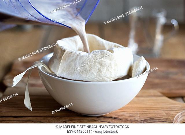 Preparation of poppy seed milk - straining the milk through a milk bag