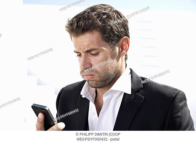 Tired businessman in black suit with mobile phone