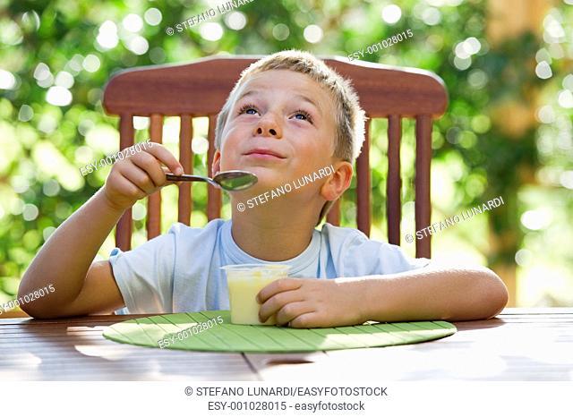 Cute little boy eating oudding outside