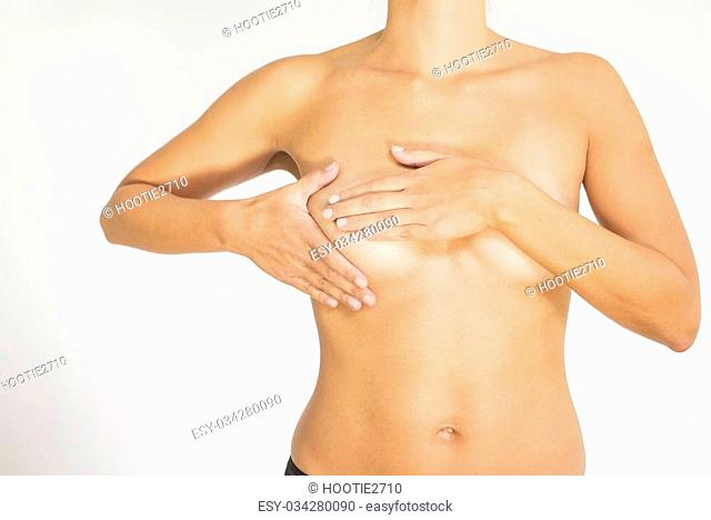 Close up view of the naked torso of a woman testing her breast for cancer flattening the tissue with one hand and manipulating to detect lumps with the fingers...