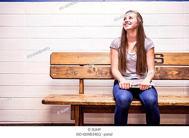 Teenage high school girl sitting on bench with notebook on lap in corridor