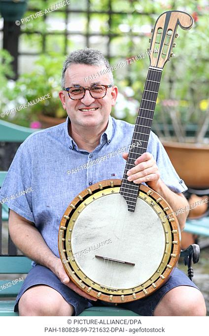 20 August 2018, Germany, Markneukirchen: Hobby instrument collector Stefan Goetze sits in the garden with an old banjo. While restoring the instrument from the...