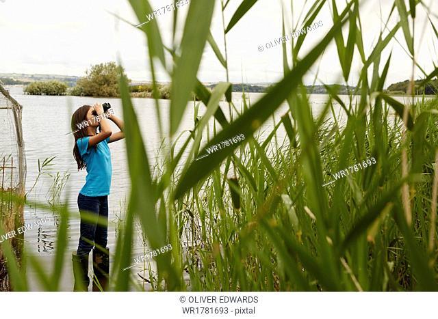 A young girl, a birdwatcher with binoculars