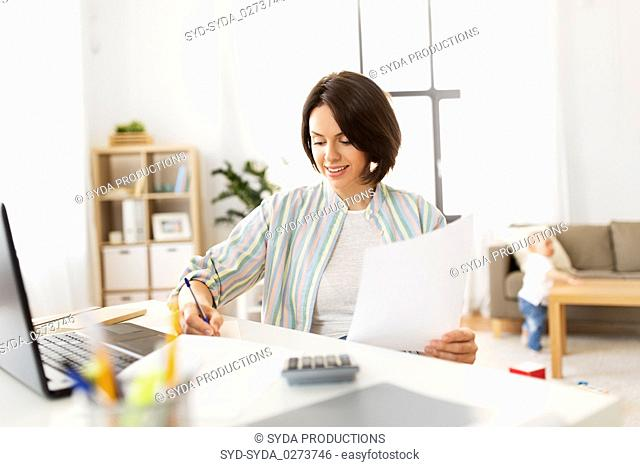 mother working with papers and baby boy at home