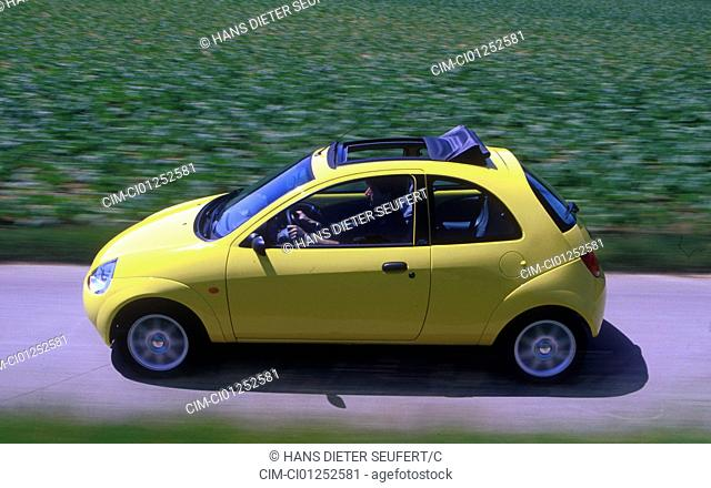 Car, Ford Ka 1.3i, small approx., Limousine, model year 1996-2002, yellow, driving, diagonal from the front/oben, side view, country road