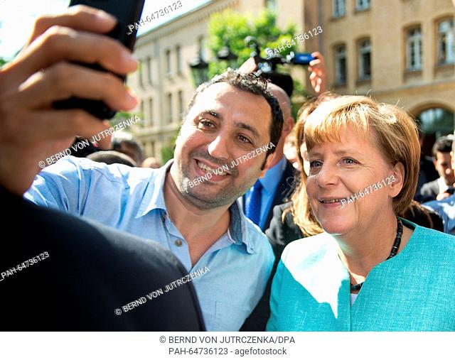 ARCHIVE - An archive picture dated .10 September 2015 shows German Chancellor Angela Merkel having a selfie taken with an asylum seeker at a processing centre...