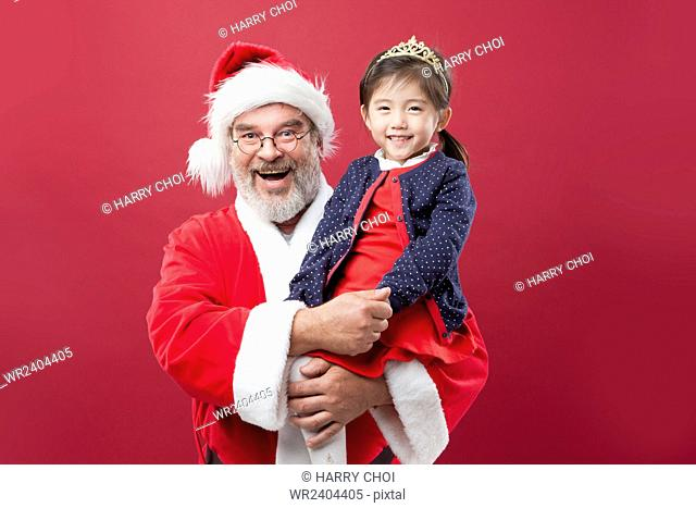 Portrait of smiling Santa holding a smiling girl staring at front
