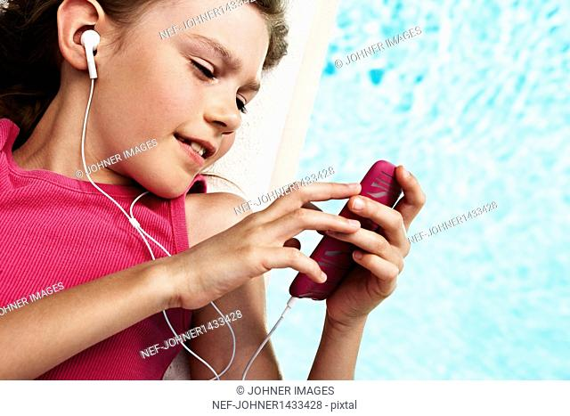 Girl with mp3 player on pool raft