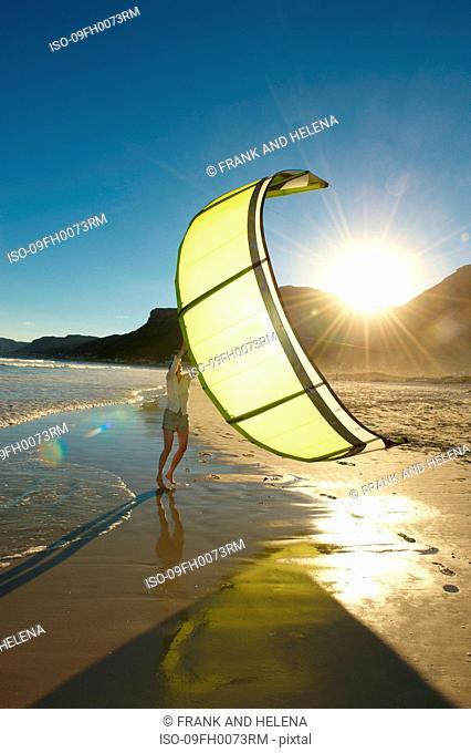 Woman holding kitesurfing sail on beach