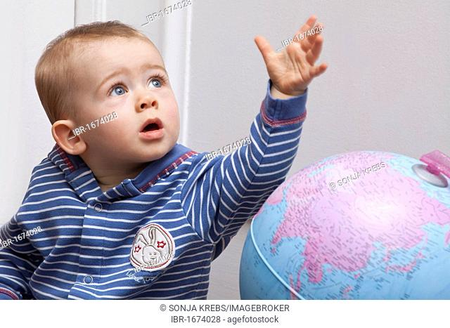 Boy, baby, eight months, with globe
