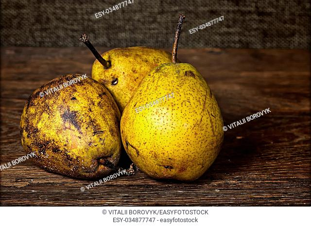 Three old pears on a wooden table background sacking