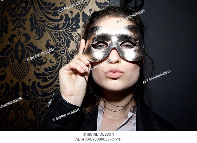 Woman wearing party mask, pursing lips, portrait