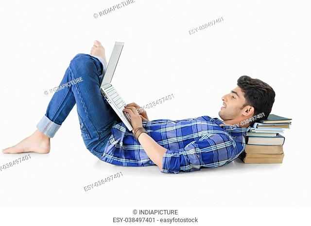 Happy Indian man lying on floor using a laptop PC