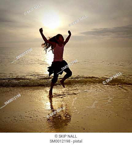 Little girl jumping in the ocean