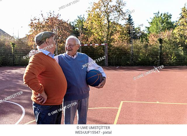 Two fit seniors having fun on a basketball field