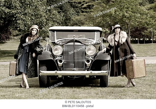 Caucasian women with luggage by vintage car