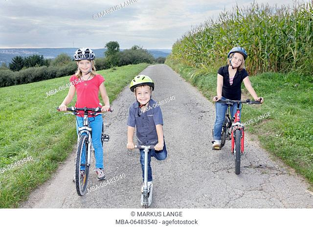Boy with Scooter and two girls on a bicycle