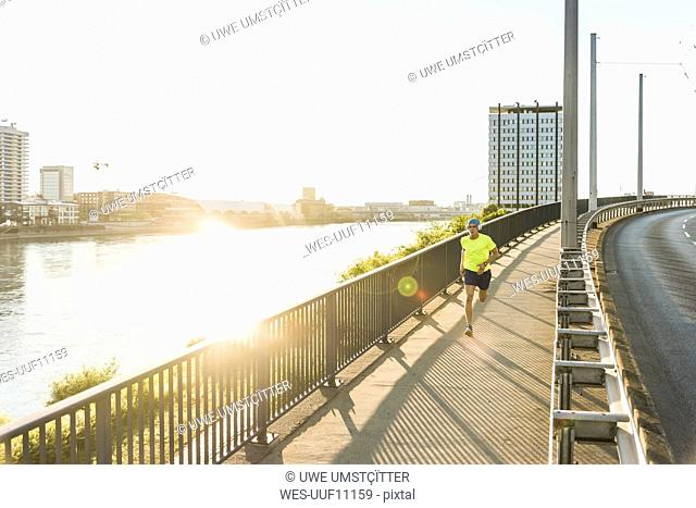 Young athlete jogging on a bridge in the city