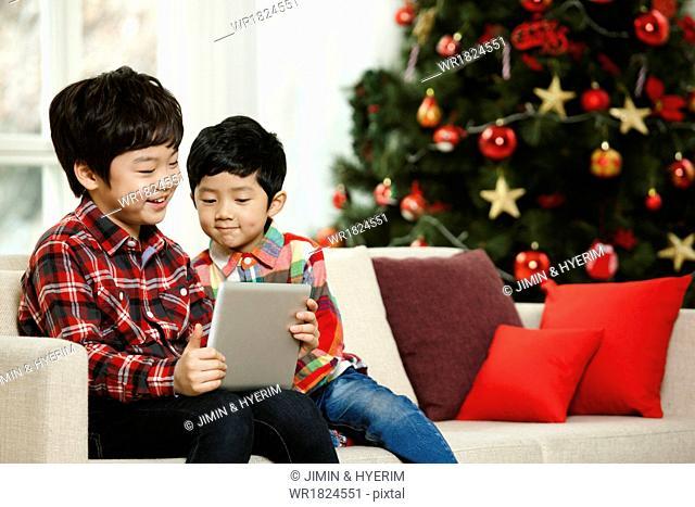 Two boys sitting next to a Christmas tree