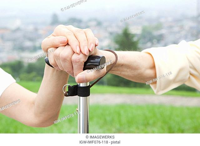 Japan, Tokyo Prefecture, Senior couple's hand holding walking stick, close-up