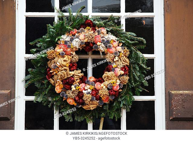 A beautiful Christmas wreath hangs on the door of a colonial home in Virginia