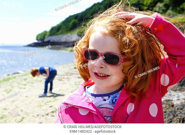 Little girl in sunglasses on the beach at Aberdovey Aberdyfi in Wales
