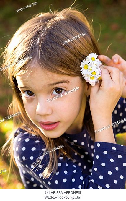 Portrait of little girl wearing daisies