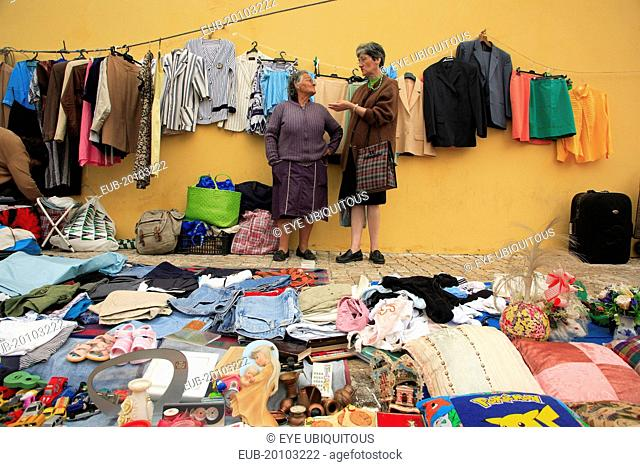 Feira da Ladra fleamarket or the Thieves Market in the Alfama district. Two women talking standing surrounded by display of clothing and other items for sale