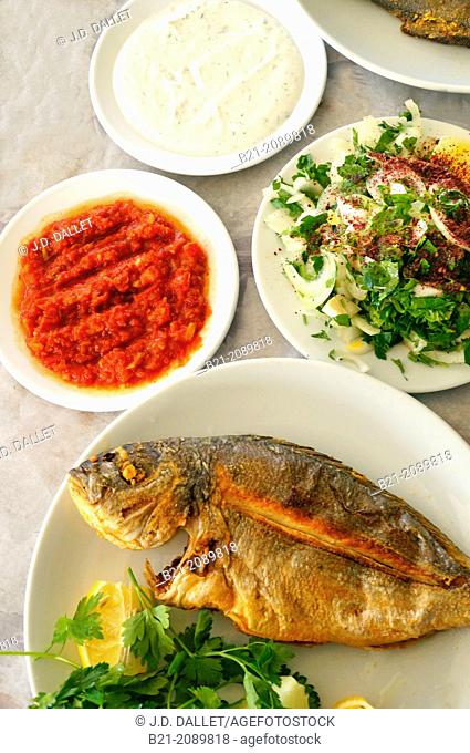 Fish from the Beysehir Gölü lake, with salads of hot tomatoes, yogurt with cucumber and parsley with onions, Central Anatolia, Turkey