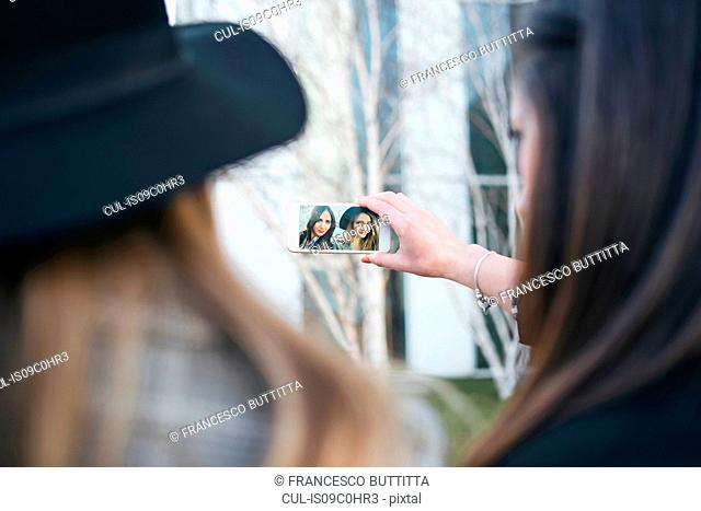 Two young women taking smartphone selfie in city, over shoulder view