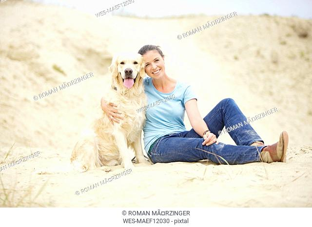Smiling young woman with dog in sand