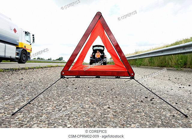 Reflective warning triangle in front of a broken down car, with a man calling for assitance from the booth of his car, whilst a fuel truck passes by