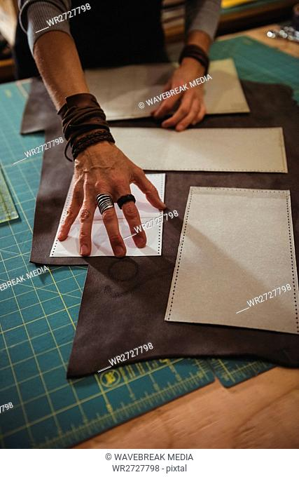 Craftswoman arranging leather piece on work tool in workshop