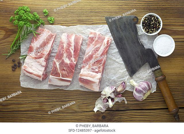 Raw pork ribs with a cleaver and various ingredients on a wooden surface