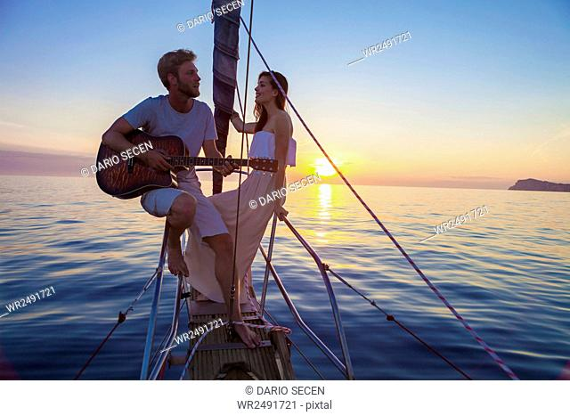 Young man playing guitar on sailboat at sunset