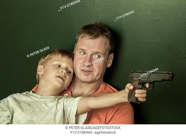 Young boy, holding a toy gun, with his father