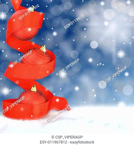 Red Christmas balls with ribbon on snowy background