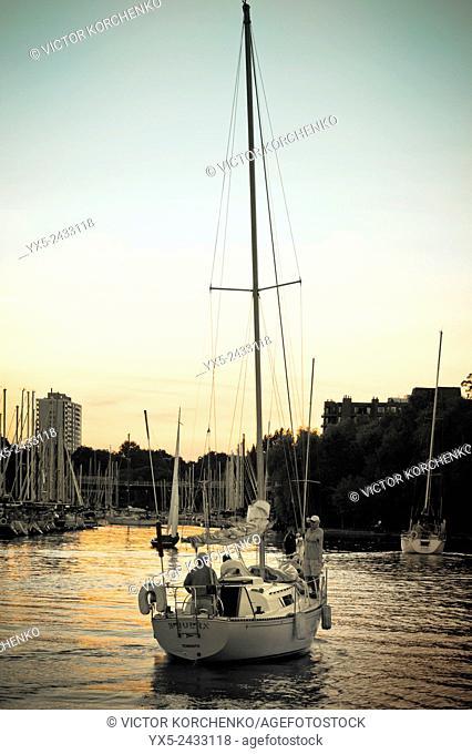 Yacht with sails down entering Oakville marina on lake Ontario