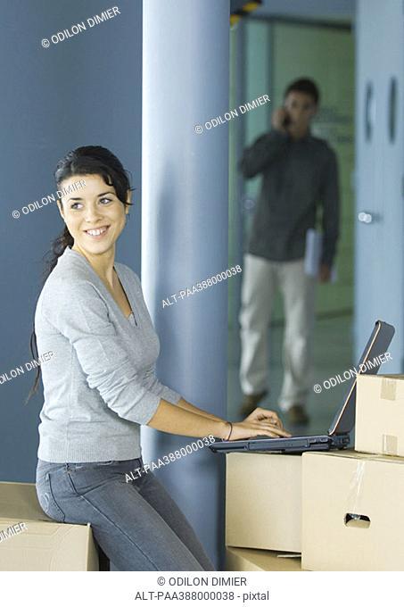 Young woman using laptop on cardboard box