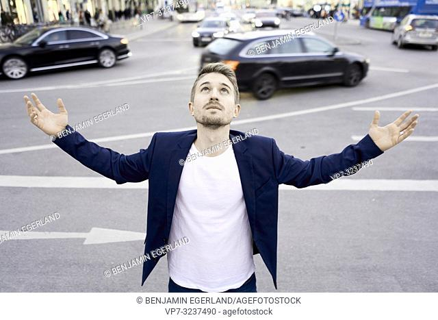 business man with open arms at street in city next to traffic, looking up, in Munich, Germany